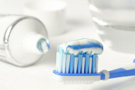 Herkoemmliche Zahnpasta auf Zahnbuerste