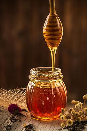 Honig, der von einem Holzlöffel in ein Glas fließt