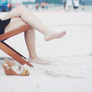 Frau im Liegestuhl mit weißen Beinen