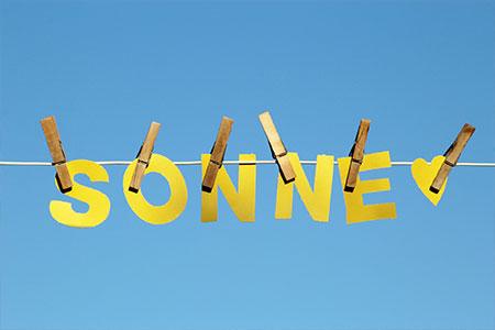 """""""Sonne"""" geschrieben mit Papierbuchstaben auf einer Wäscheleine"""