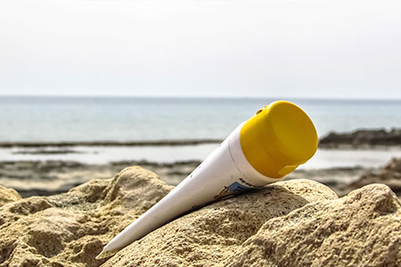 Sonnencreme, die im Sand liegt